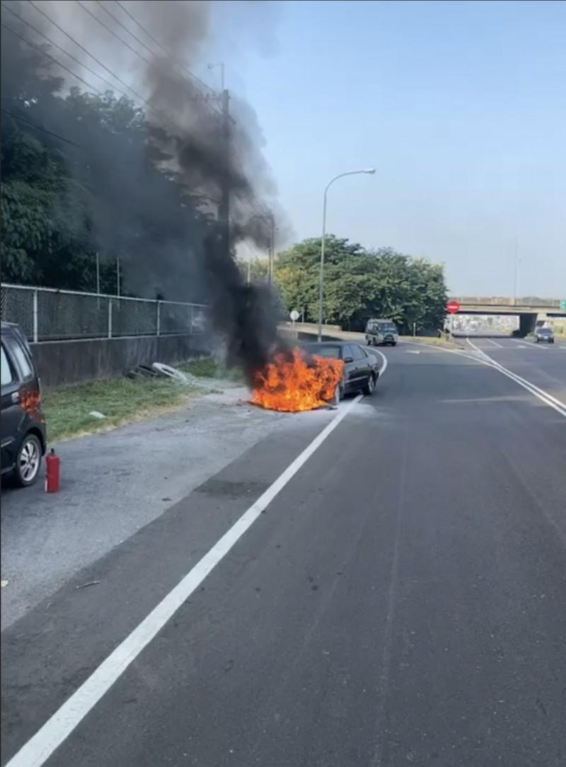 1輛轎車停靠在下岡山交流道的路邊起火。(記者許麗娟翻攝)