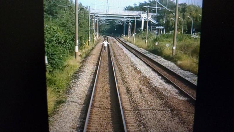 白衣男在台鐵鐵軌上張開雙手做擋車動作。(記者王俊忠取自臉書「台灣便當管理局-附屬鐵路部」)