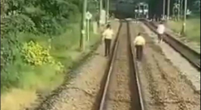 兩名台鐵保安站員工跟隨闖進鐵軌區的白衣男(後右一)。(記者王俊忠取自臉書爆料公社)