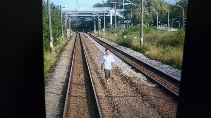 闖鐵軌區的白衣男朝台鐵區間車方向走來。(記者王俊忠取自臉書「台灣便當管理局-附屬鐵路部」)