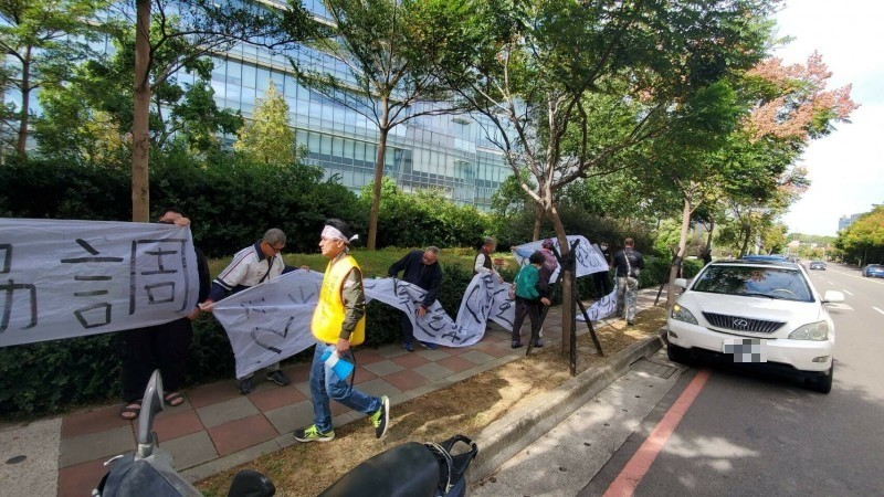 自救會在說明會前到台積電總部前拉白布條抗議。(記者黃美珠攝)