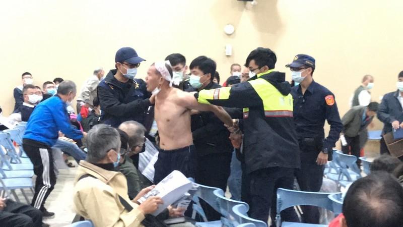 員警一湧而上制止徐男繼續砸雞蛋自虐,把他短暫帶離會場。(記者黃美珠攝)