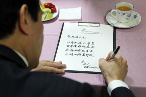 圖為總統馬英九俯首提筆寫字的畫面。(圖片擷取自馬英九總統臉書)