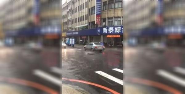 民眾今天下午2點拍下新莊區道路人孔蓋,疑似不堪負荷瞬間大雨的排水流量,不斷躍出路面。(圖擷取自影片)