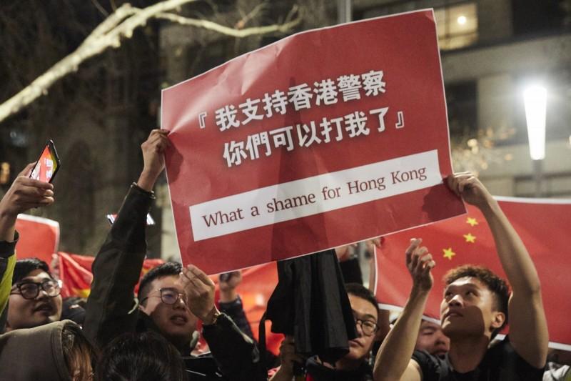 墨爾本集會現場有數名撐中人士搗亂,手持「我支持香港警察,你們可以打我了」的橫布條或標語。(歐新社)