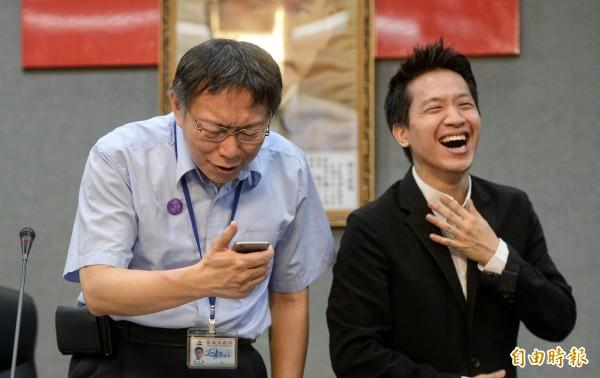 民進黨議員何志偉用手機找來「可達鴨」照片給他看後,柯文哲大笑說「我看不出哪個地方像我」!(記者林正堃攝)