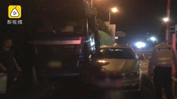 一名駕駛在開車進收費站時,因為貪快而突然改變車道,結果發生擦撞,被夾在大卡車與收費站護欄間。(圖擷取自梨視頻)