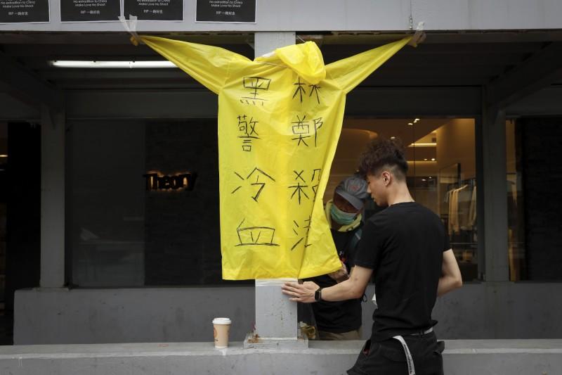 遊行現場出現了寫著「林鄭殺港,黑警冷血」的黃色雨衣。(美聯社)