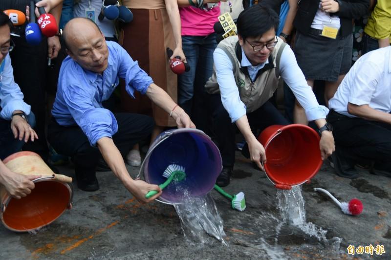韓、陳於金獅湖市場傾倒積水。(記者張忠義攝)