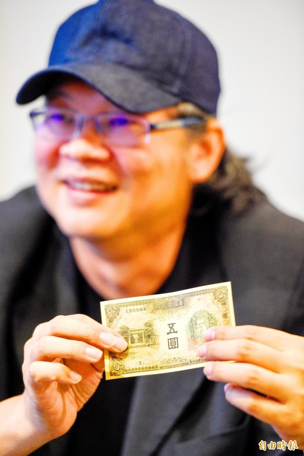 Director Kent Chang holds up a Japanese-era banknote during an interview in Taipei on Oct. 8. Photo: George Tsorng, Taipei Times