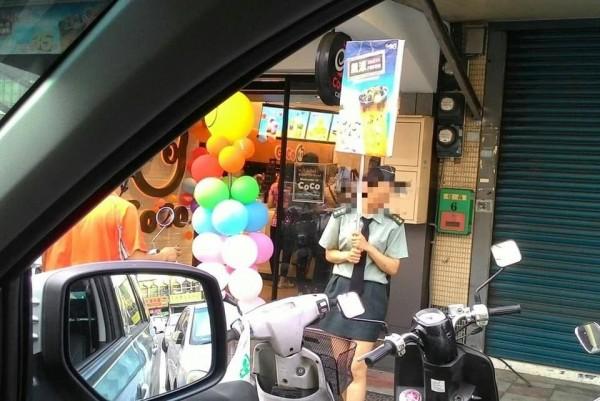 網傳知名連鎖手搖飲料店讓女店員穿上「全套陸軍女軍官」服裝,在街頭舉牌宣傳,引發不少職業軍人反彈,國防部更決定提告。(林姓網友提供)