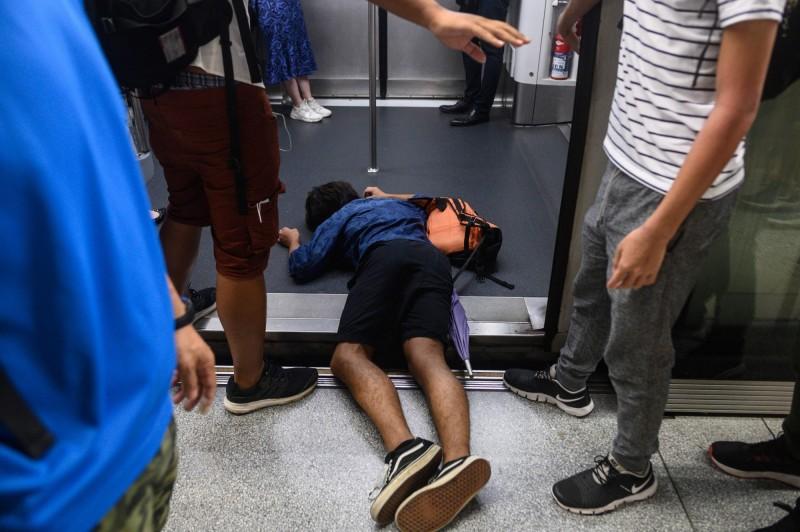 今早香港地鐵各線出現多名民眾,擋在車門中間阻止關門,或在車內按下緊急停車鈕令列車急剎,多條線暫停行駛。(法新社)