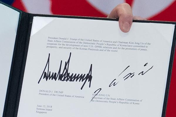 今天下午1時40分,川普、金正恩共同簽署文件,為了展現豐碩成果,川普還秀出文件上的簽名。(法新社)