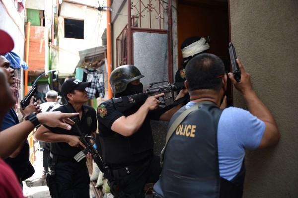 菲國警方持搜索票在巴石市(Pasig City)與毒品牽連的民宅荷槍實彈搜查。(法新社)