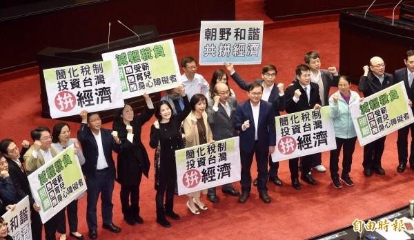 民進黨立委在議場前高舉標語,慶祝順利通過法案。(記者羅沛德攝)