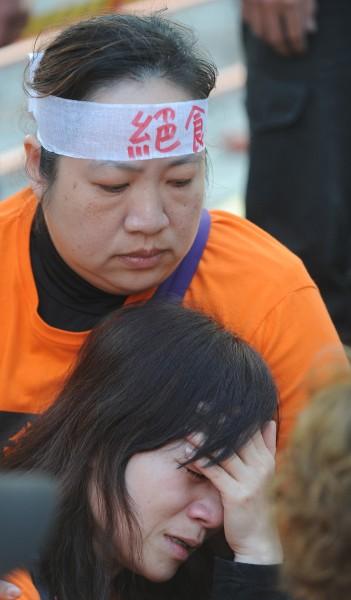警方開始抬離行動,收費員看到同伴一一被抬上警車,不禁流下淚來。(記者劉信德攝)