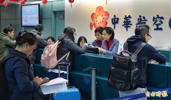 桃園機場今(11日)天華航班機共有22架次取消(出境9個航班,入境13個航班),預估影響旅客人數約3893人。華航櫃檯人員則是忙著為旅客處理轉機事宜。(記者劉信德攝)