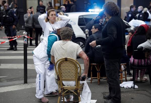 一名受傷男子在現場接受治療。(法新社)