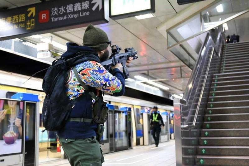 演練中,一名志工站在捷運月台,扮演拿著步槍的恐怖份子。(圖擷取自NPA署長室)