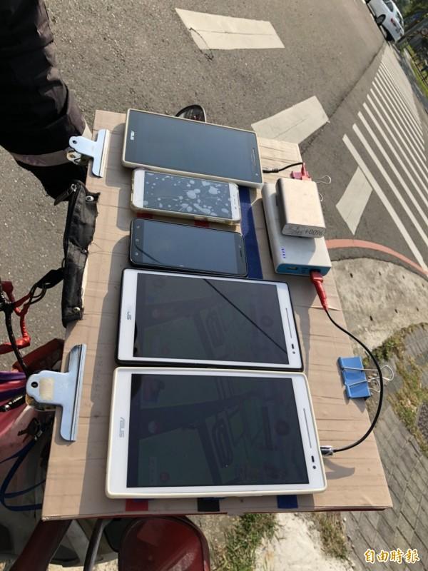 寶可夢迷莊姓男子在機車儀表板上架設板子,利用魔鬼沾,將3支平板、2支手機和行動電源黏貼上去,便可一次擺放5支。(記者廖雪茹攝)
