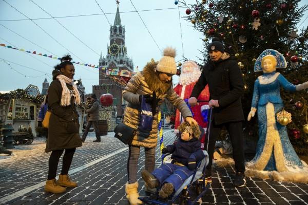 俄羅斯遊客與當地耶誕節故事才有的「雪女」(Snow Maiden,圖右藍色雕像)合照。(美聯社)
