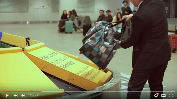 旅客拿起行李,發現藏在底下的「機會命運」。(圖擷自YouTube)