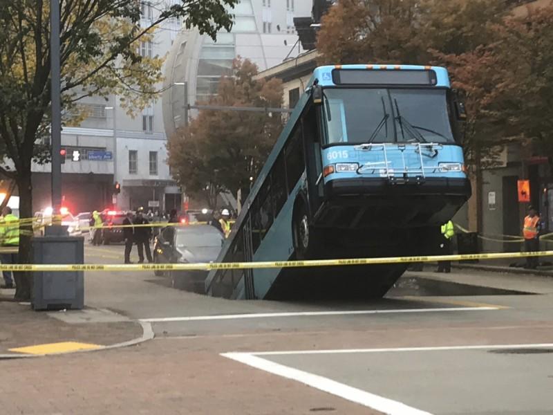 美國近日發生公車被馬路突現的坑洞「吃掉」奇景。(美聯社)