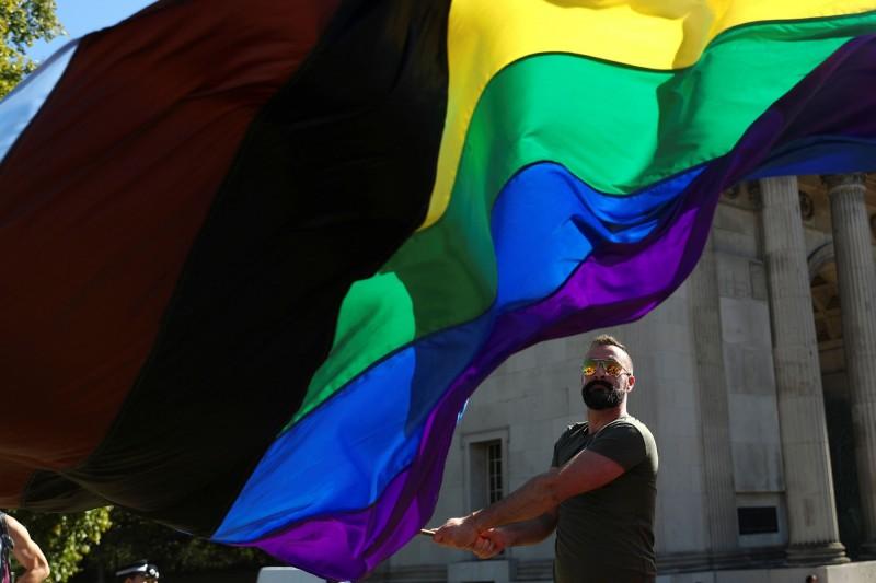 倫敦的Trans Pride March遊行中,一名參與者揮舞彩虹旗。(路透)