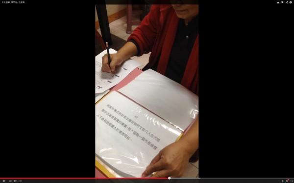 在問卷進行中,民調員還不斷翻開抹黑柯P的文件,企圖影響受訪者。(圖擷自YouTube)