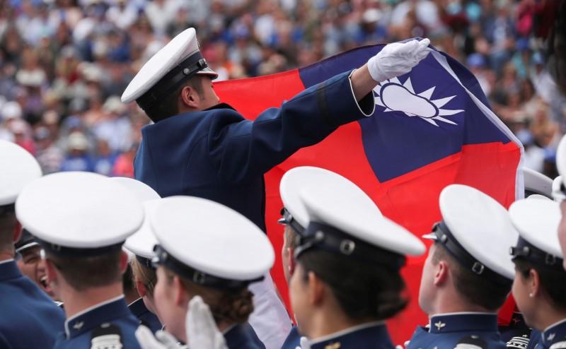 我國畢業生開心拿起國旗揮舞。(路透)