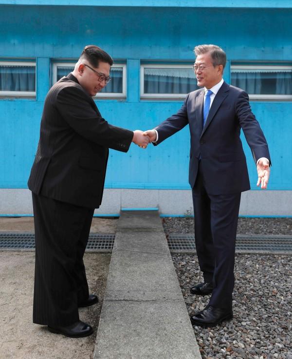 金正恩與文在寅在南北韓軍事分界線握手,金正恩隨即牽著文在寅的手走向北韓,讓在場人士大吃一驚,因為這根本不在預計行程裡,不過隨後2人又走回南韓。(美聯社)