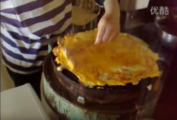 老闆娘將蛋一顆顆打上煎餅皮上,慢慢的煎餅變成超厚蛋餅。(圖擷自YouTube)
