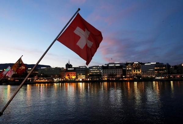 瑞士選民明確否決要讓國內法律凌駕國際法的公投案。圖為瑞士日內瓦商業金融區前的一面瑞士國旗。(路透)