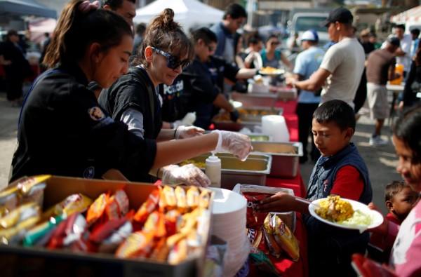 在美墨邊界,有許多孩子在庇護所排隊領取他們的耶誕餐。(路透)