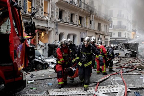 消防員抬著傷者送往救護車。(法新社)