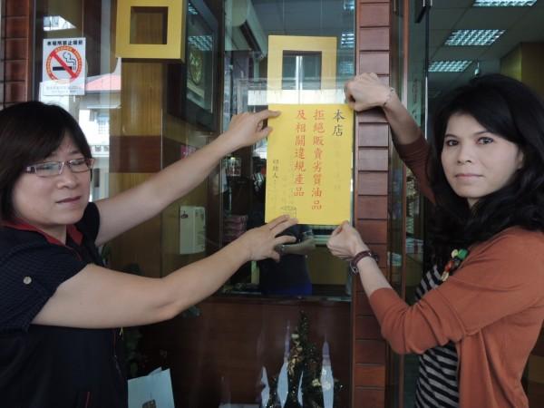 衛生局食品衛生科長徐仁霞(左)與恩典方塊酥老闆娘呂妍妍(右)在店門口張貼該店拒用劣質油及目前使用油品品名的切結書。(記者余雪蘭攝)