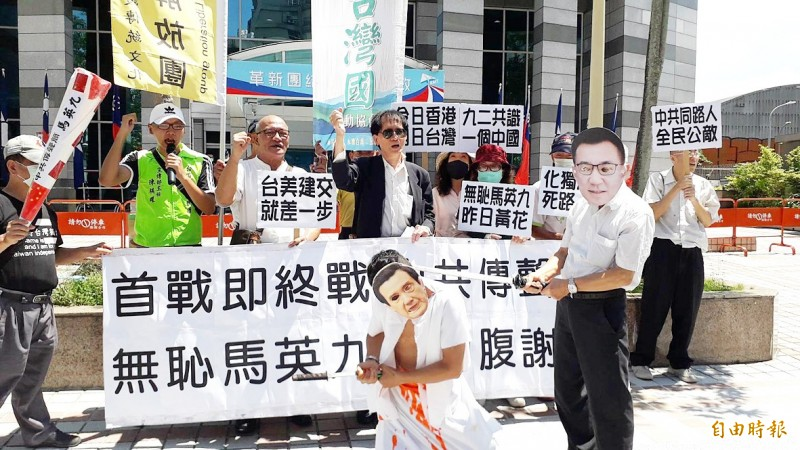 Taiwan Republic Office members perform a skit in front of the Chinese Nationalist Party (KMT) headquarters in Taipei yesterday in which KMT Chairman Johnny Chiang is shown decapitating former president Ma Ying-jeou as Ma commits hara-kiri. Other protestors hold placards demanding that Ma apologize for having said that Taiwan would lose in a war with China.  Photo: Jason Pan, Taipei Times
