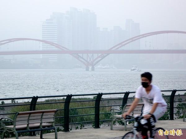 圖為關渡地區遠眺淡水河對岸,只見左岸一片灰濛濛,岸邊建築物已被霧霾掩蓋。(資料照,記者朱沛雄攝)