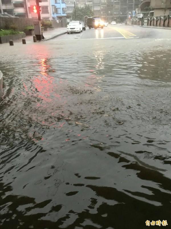 基隆市今早大雨再下,獅球路成功國小大門前積水,許多車輛強行通過。(記者俞肇福翻攝)