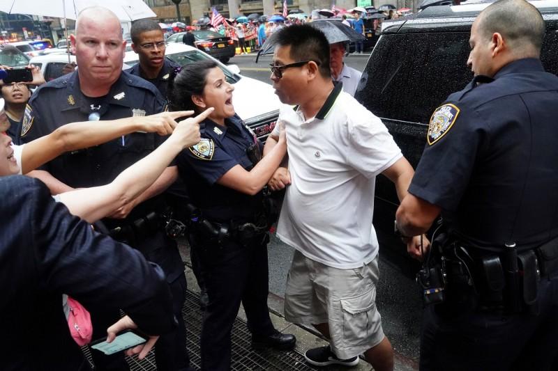 一名鬧事男子被警方制伏,並帶上警車隔離。(路透)