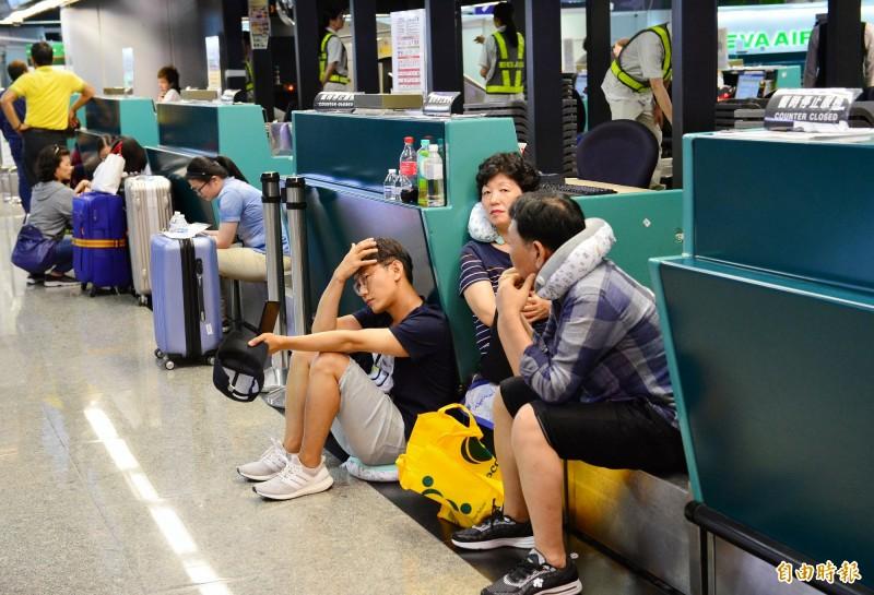 航班受影響的旅客在桃園機場第二航廈出境大廳等候簽轉其他航空公司航班,席地休息。(記者朱沛雄攝)