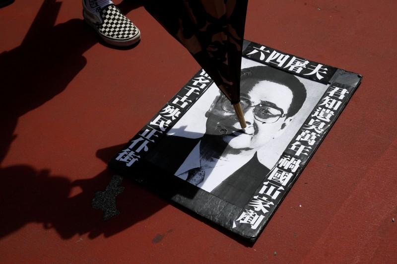 部分人士同時帶著李鵬的照片到現場「哀悼李鵬」。(路透)