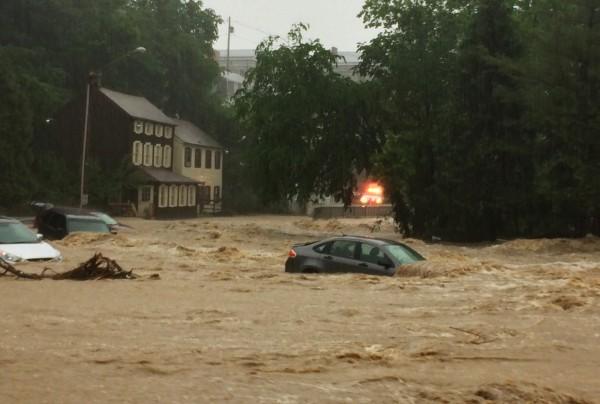 當地河流暴漲,洪水傾瀉至街道上,大量洪水將路邊車輛直接帶走,一度淹到2層樓高。(美聯社)