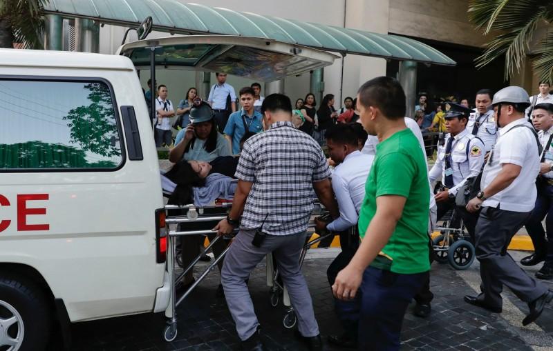 地震後,救援人員把一名婦女帶上救護車。(美聯社)