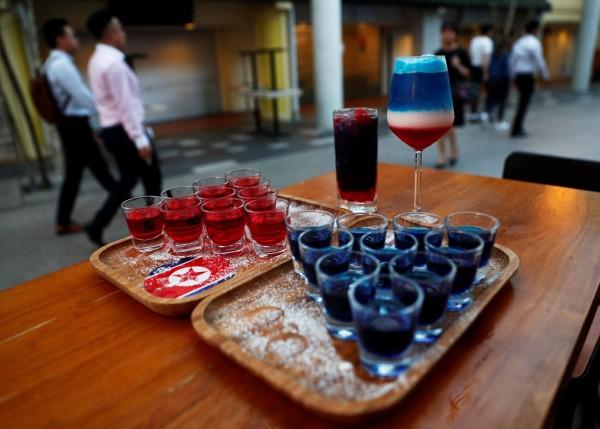 被排成三角形的10小杯藍色與紅色調酒,是「川與金」調酒,藍色以波本威士忌為基酒,紅色則以韓國的燒酒為基酒。(路透) ☆飲酒過量  有害健康  禁止酒駕☆