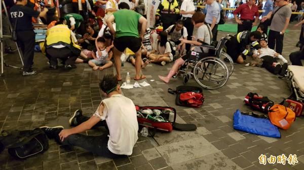 受傷的旅客坐在車站內等待救援。(記者陳志曲攝)