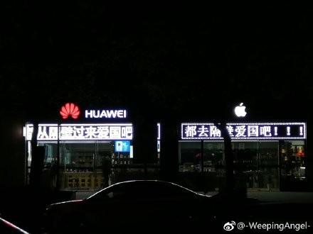 中國網友發現,一家與華為專賣店相鄰的蘋果專賣店,竟出現「都去隔壁愛國吧」跑馬燈。(擷取自微博)
