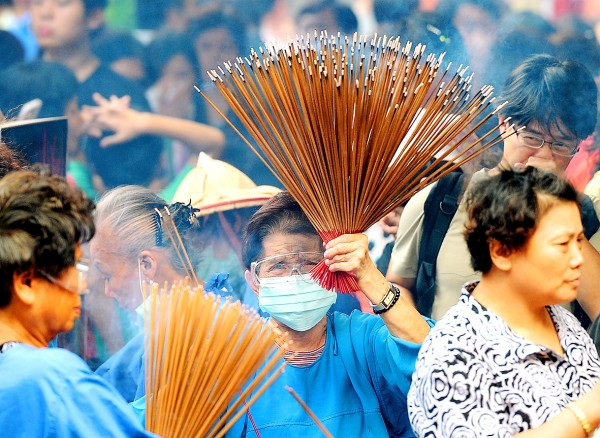 Volunteers wearing surgical masks and goggles offer joss sticks to worshipers at the Xingtian Temple in Taipei on Monday. The temple has asked people to stop burning incense and offering food items starting yesterday. Photo: Chu Pei-hsiung, Taipei Times