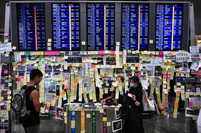 機場航班螢幕被以接龍方式,貼滿寫上希望小語的便條紙。(法新社)