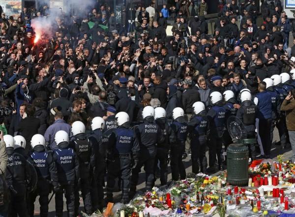 比利時布魯塞爾恐攻引發全球關注,今天民眾聚集在交易所廣場向臨時紀念碑為罹難者哀悼,但遭身穿黑衣的極右派闖入示威。(路透)